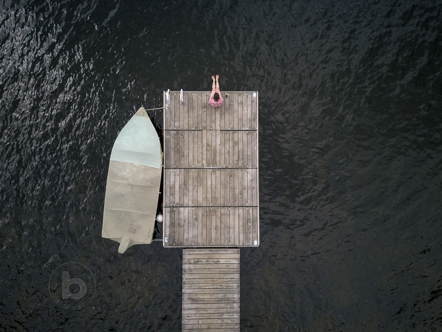 Aerial photo of a woman (40) sitting on a wooden dock at a lake in the Kawartha cottage region near Haliburton, Ontario, Canada