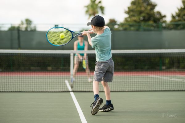 Boy and mother enjoy leisure time on summer Florida vacation playing tennis