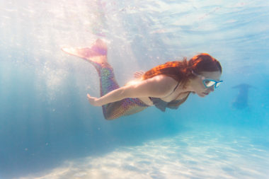 Underwater view of woman on holiday swimming in pool with colorful mermaid tail