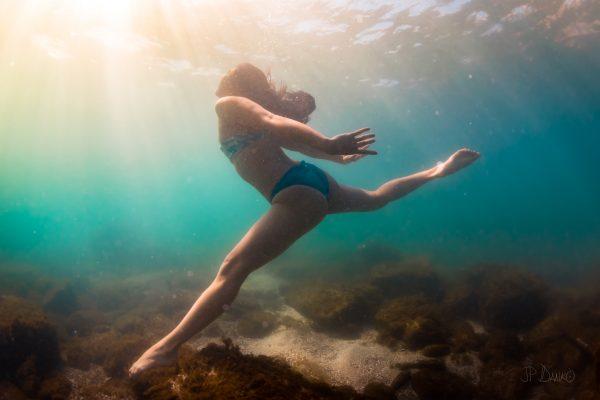 Woman in bikini diving exploring shallow blue green waters of Lake Ontario