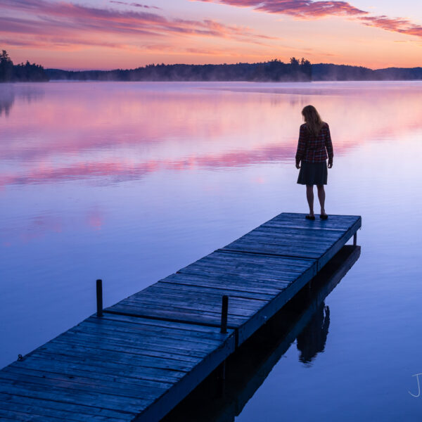 Woman (43) on cottage dock with colorful summer sunrise.