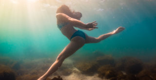 Woman in bikini diving exploring shallow blue green waters of Lake Ontario